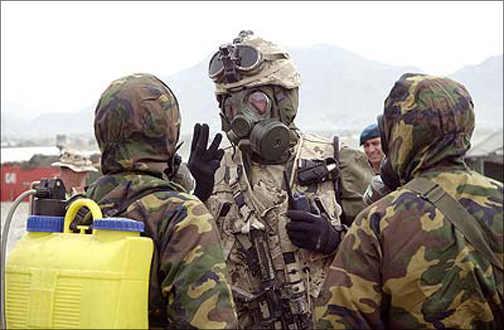 Three soldiers dressed in chemical suits.
