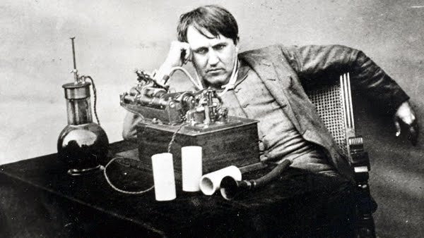 A photo of Thomas Edison, in a slouching pose behind some of his inventions.