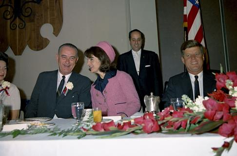 A photo of Jackie Kennedy talking to Lyndon Johnson at a banquet.