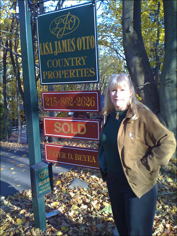 A photo of Nancy Birnes in front of our house's Sold sign.